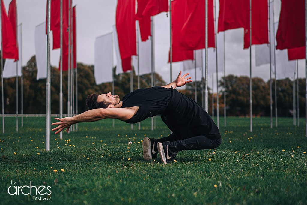 Dancer Sam Buswell from 2Faced Dance Company performs beneath the flags of In Memoriam by Luke Jerram