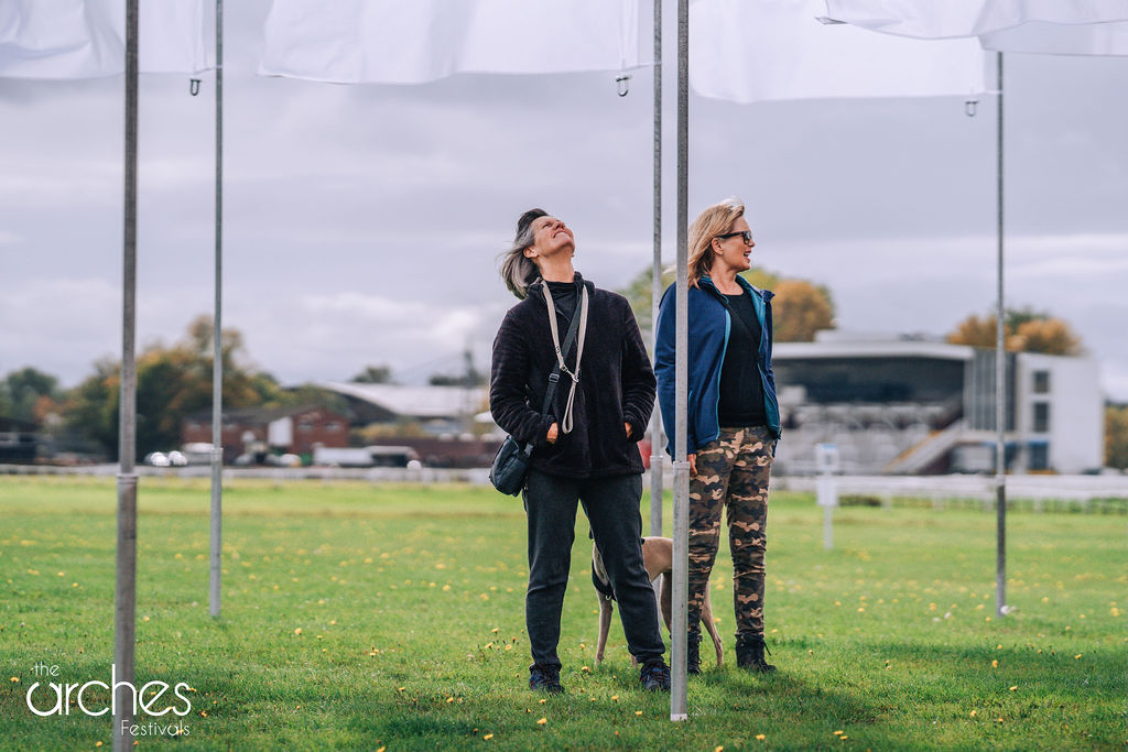 Dog Walkers pause whilst exploring the flags of In Memoriam by Luke Jerram