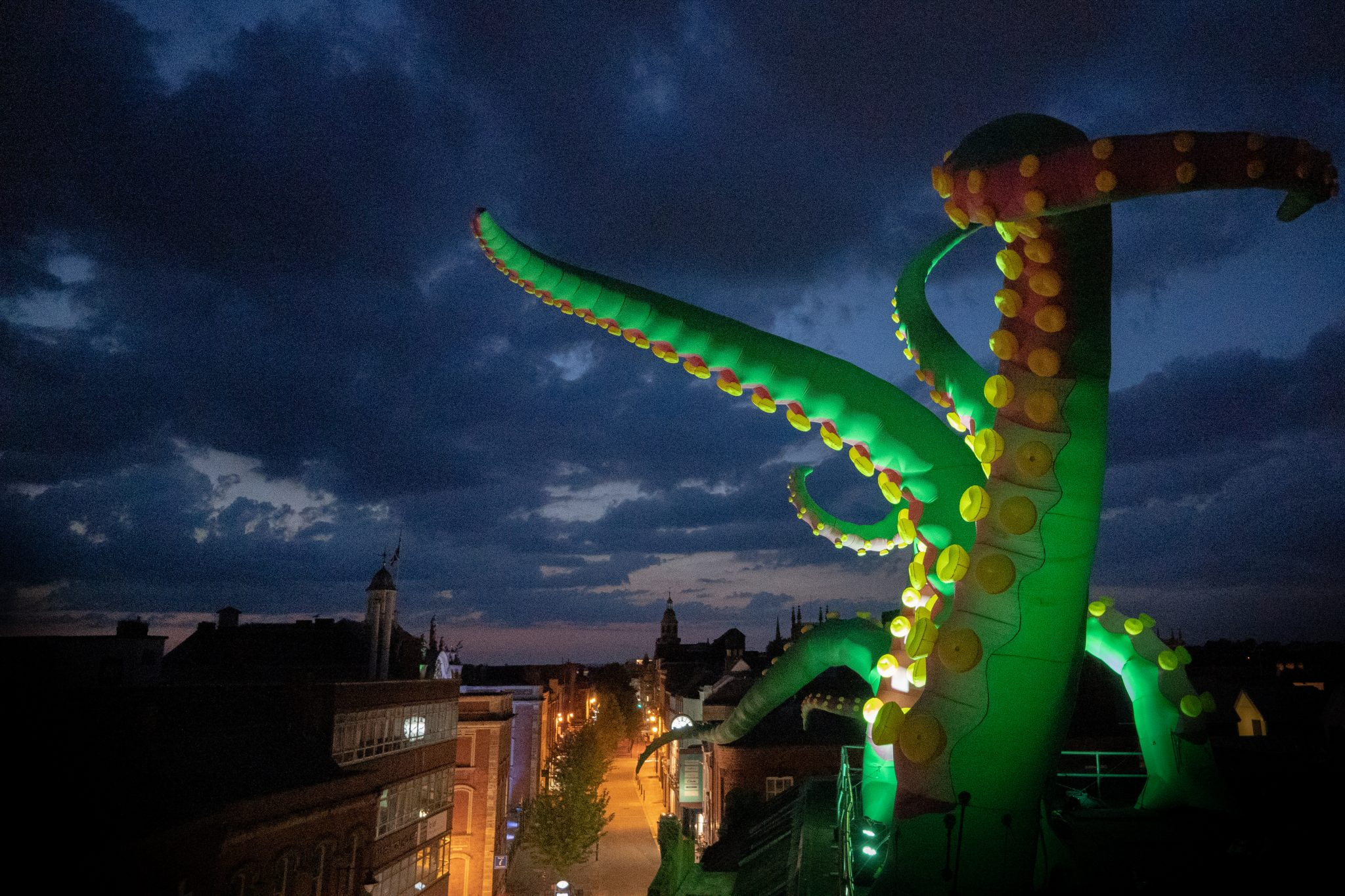 Image Description: : Photo taken at night from the roof of a building where large green inflatable tentacles are lit up and are reaching out in different directions. Below you can see the high street shops lit by street lights.