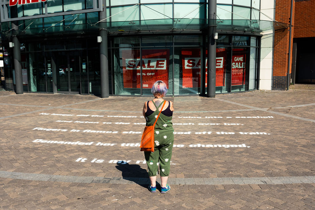 Image Description: A woman stands in the middle facing away from the camera, she is wearing a green jumpsuit with a white pattern, an orange bag and blue shoes. She is looking towards the ground where we can see a poem has been stenciled onto the pavement in large white text. In the background we can see a shop with some 'sale' signs in the window.