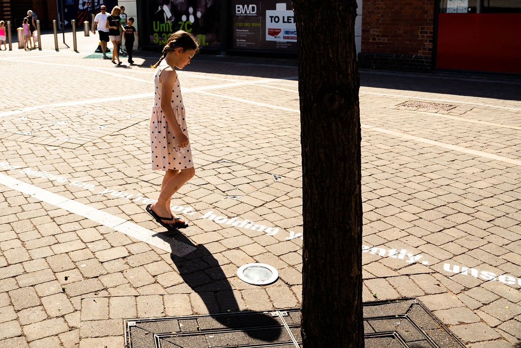 Image Description: A little girl stands sideways showing us her profile, she is wearing a white dress with black polka dots, dark flip flops and her hair is in a plait. She is looking down at the pavement where she is reading the poem that has been stenciled onto the street in large white text. In the background we see pedestrians and shops and in the foreground we can see the trunk of a tree.