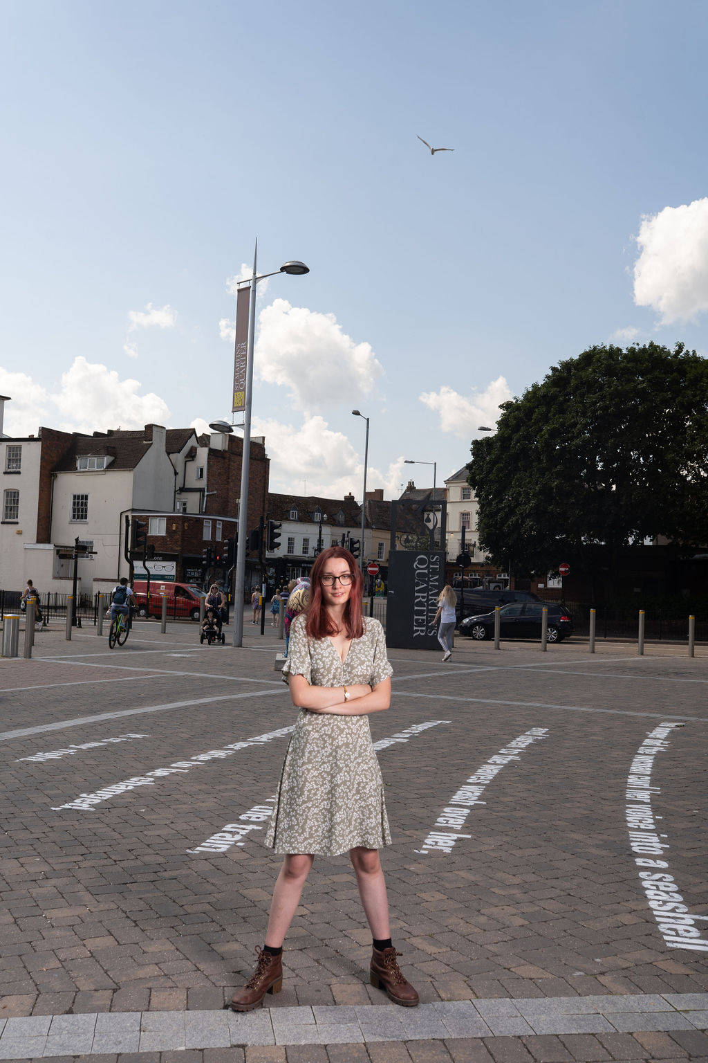 Image Description: A young woman stands in the center of the fram looking straight into the camera, she is wearing a light green patterned summer dress, dark boots, glasses and her hair is down. She stands with her feet slightly apart and her arms folded, looking very powerful. She is standing in a square and behind her on the pavement we can see her poem that has been stencilled onto the street in large white text. In the background we can see the blue sky, a sea gull flying a bove and buildings and pedestrians in the distance.