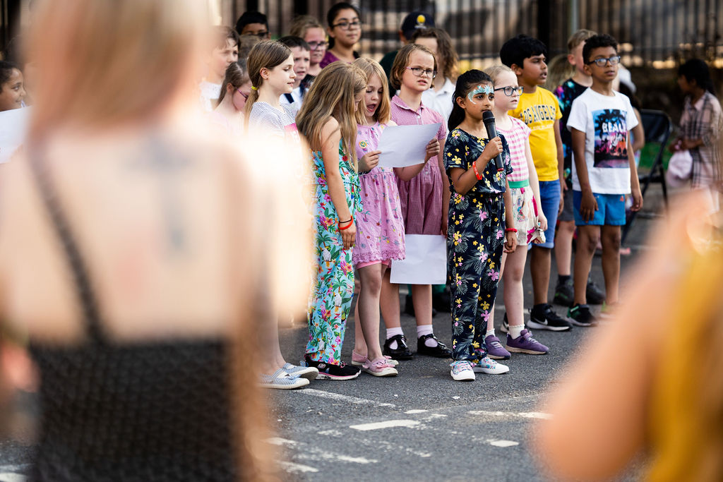 Image description: A young group of school children stand in a group facing slightly to the right of the camera where the audience are. A young girl wearing a jumpsuit and facepaint is holding a microphone and singing into it. Other school children stand beside and behind her singing, some looking at the lyrics on a piece of paper. In the foreground we can see the back of audience members watching the performance.