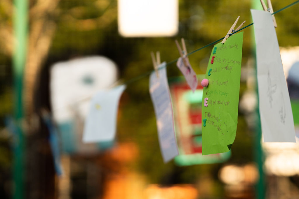 Image description: We can see a washing line has been hung up and there are multiple pieces of colourful paper that have been hung up on the line. The main one in focus in the image is a green piece of paper that has an acrostic poem on it, and while we can't see what the poem itself says we can see the word 'Recovery' has been drawn down the side of the page with each letter being a different colour. In the background we can see more art and poems that have been put up.