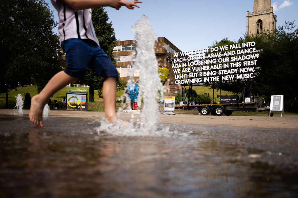 Image description: In the foreground we see water shooting up from the ground as part of a street fountain, we can see the bottom half of a little boy who looks like he is about to kick the water with his foot. Behind this we can see a large lit up poem attached to a metal trailer which is holding it up. In large white text the poem says 'At what point do we fall into each others arms and dance again loosening our shadow? We are vulnerable in this first light, but rising steady now, crowning in the new music.'. In the background we can see some signs, a couple of buildings and a blue sky.