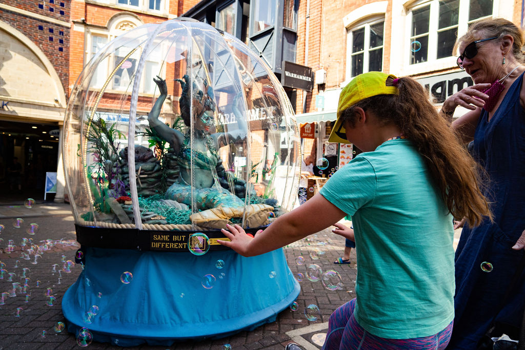 Image description: In the image there is a large glass globe, like a snow globe but much bigger, with a woman inside dressed as sea nymph. Her skin is blue, she has a scaly tail like a mermaid, and she is surrounded by seaweed and other ornaments you might find in the sea. Outside the globe a young girl wearing a blue T-shirt and yellow hat stands next to an older woman. The young girl has her arms outstretched and is touching the bubbles that are surrounding the globe. Bubbles fill the air and seem to be coming from the globe. On the globe itself we can see a yellow sticker with a QR code and yellow text that reads 'Same But Different. There is also a big red button just underneath the globe. In the background we can see shops and buildings indicating we are on a high street.