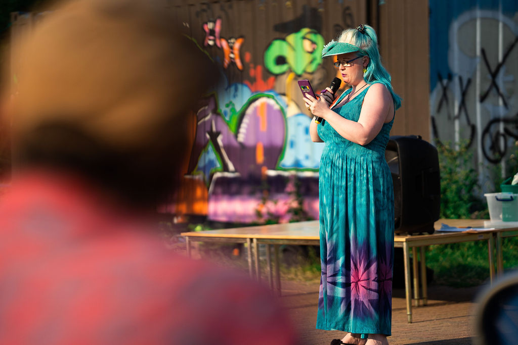 Image description: A woman stands in the center of the image, she is wearing a long blue dress with purple and pink patterns on it, she has a blue visor with a flower attached and her hair is blonde with the ends dyed a similar light blue to her visor and dress. She is holding a microphone as she reads her poem out loud, reading it on her phone which she holds in front of her. In the background we can see a stage with a speaker, and some graffiti.