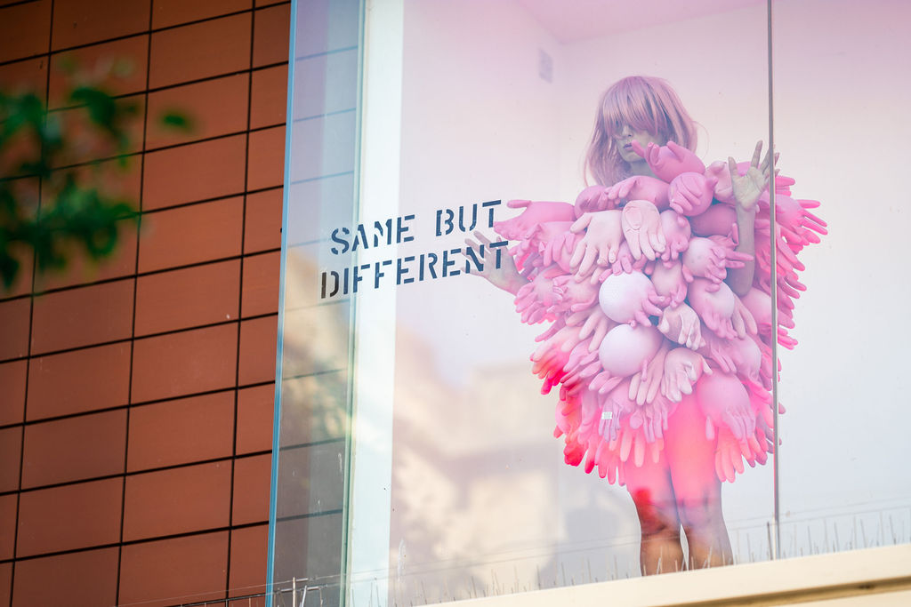 Image description: A woman stands inside a shop window looking out, she is wearing a pink wig that covers part of her face and wears a body suit entirely covered with inflated pink hand gloves. There is a vinyl on the window that says 'SAME BUT DIFFERENT' in black text.