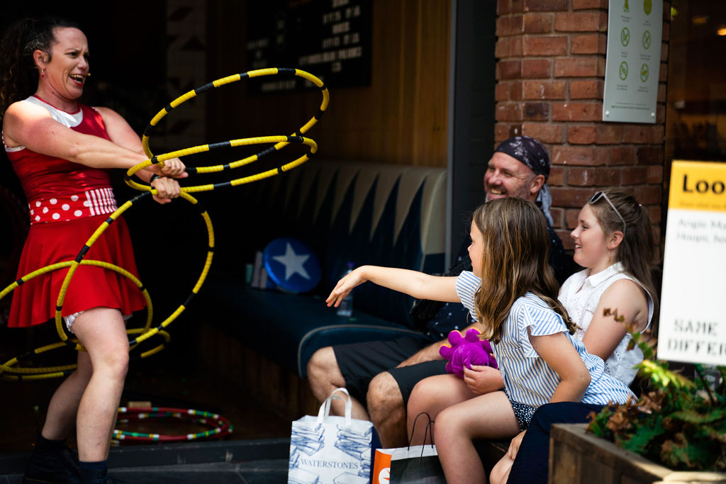 Image description: A woman is holding multiple yellow hoops, some in her hands, some on her legs and she appears to be moving. She is wearing a mic on her face and a red dress that has white stripes and polka dots across the middle section. In front of her is a family , with a couple of young children. They have shopping bags by their feet and one of them is holding a small purple octopus. The family are all smiling and laughing, and one of the young girls is reaching out her hand as if she wants to touch one the hoops the woman is holding. In the background we can see the inside of a shop with some more multi coloured hoops on the ground.
