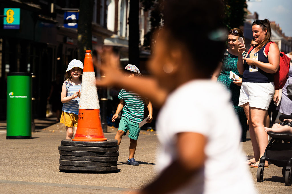 Image description: On the high street we can see an orange traffic cone with a black sticker with text that says 'Same But Different. People are stood around the cone with some adult taking photos and some children standing close by watching the cone closely.  young girl in the foreground has her hand reaching out towards the cone as though she is trying to grab it.