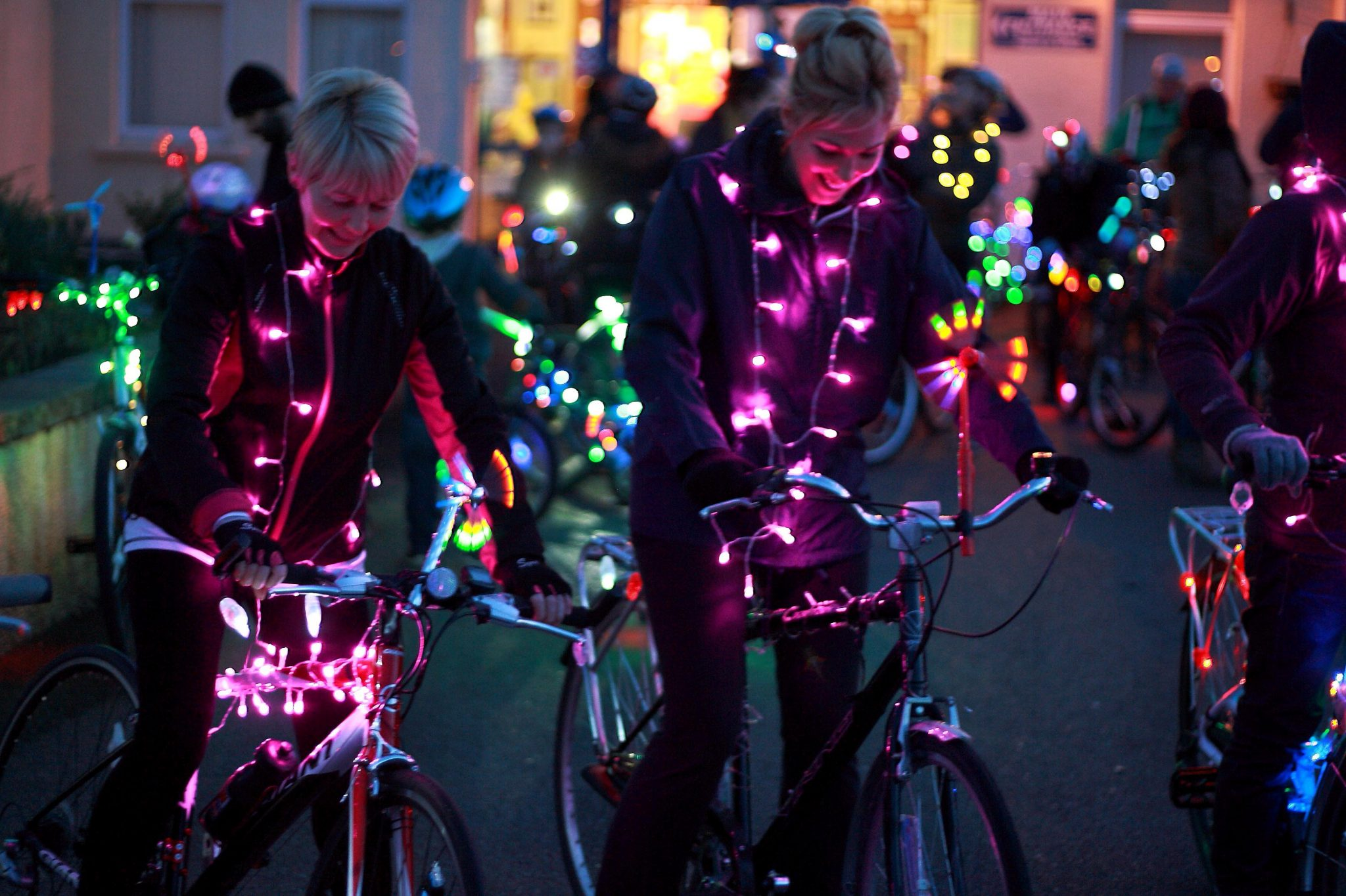 Image description: A group of cyclists are gathered together their bikes and themselves decorated with fairy lights of different colours, pink , green, blue etc. Two women at the front both smiling and looking at their bikes preparing to set off.